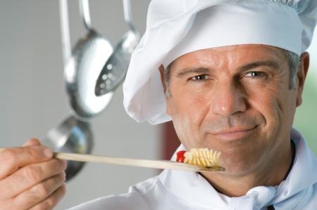 cocineras: Sonriendo satisfecho gusto del cocinero de la comida en el restaurante