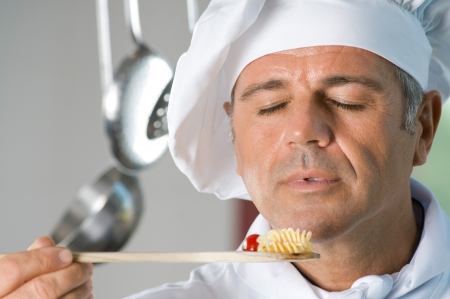 Mature satisfied chef smell the aroma of his food while cooking at restaurant Stock Photo