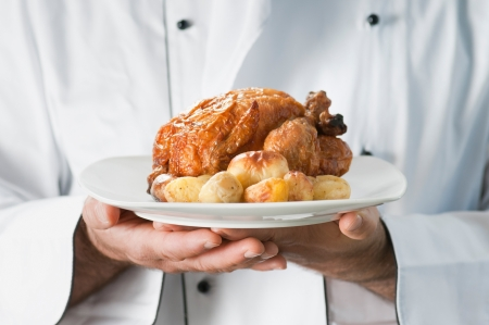 serving food: Chef presenting and serving his roast chicken with potatoes Stock Photo