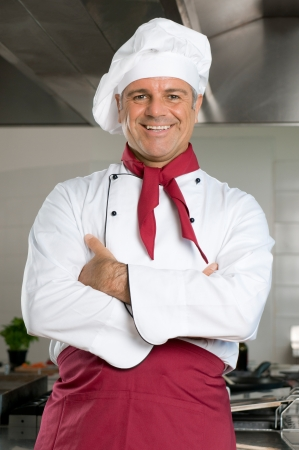 Happy smiling mature chef looking at camera in his restaurant kitchen photo