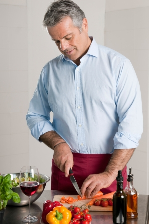 Happy mature man cutting fresh organic carrots for an healthy vegetarian lunch  photo