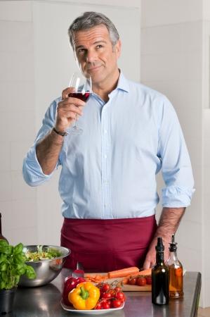 bebiendo vino: Hombre maduro degustación de una copa de vino tinto mientras se cocina en casa