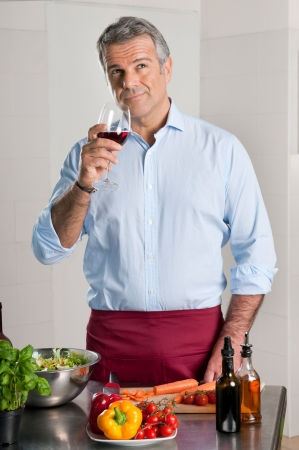 tasting: Mature man tasting a glass of red wine while cooking at home