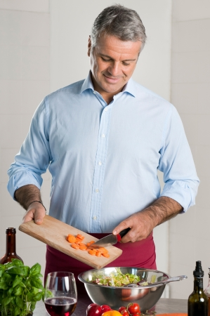 Happy mature man preparing an healthy vegetarian salad at home photo