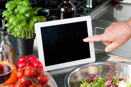 recipe: Examine digital recipe on tablet at kitchen to prepare the lunch