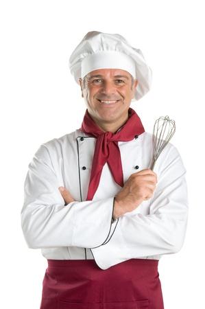 šéfkuchař: Happy starší profesionální kuchař drží šlehač a díval se na kameru, izolovaných na bílém pozadí