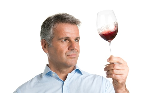 winetasting: Satisfied mature man looking at red glass of wine during a winetasting Stock Photo