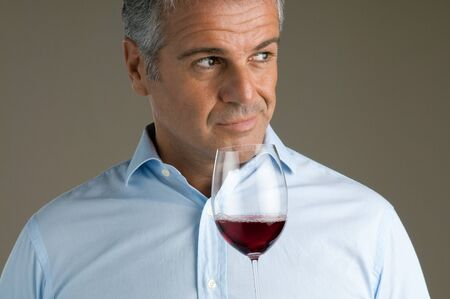 tastes: Satisfied mature sommelier smell at a glass of a red wine Stock Photo