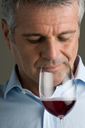 Satisfied mature man smells a red wine glass while winetasting it photo