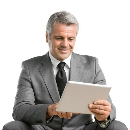 net surfing: Felice uomo d'affari sorridente maturo navigare in rete e lavorare con la tavoletta digitale isolato su sfondo bianco