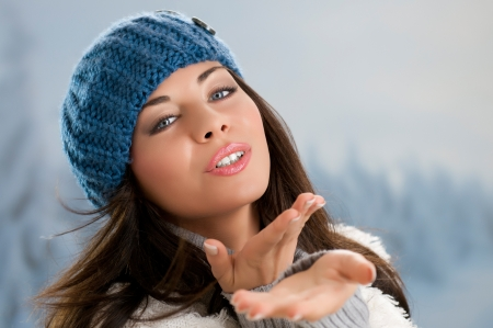 winter day: Beautiful young woman blowing a kiss in a winter day outdoor