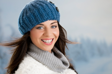 Beautiful happy young woman smiling and looking at camera in a winter day outdoor photo