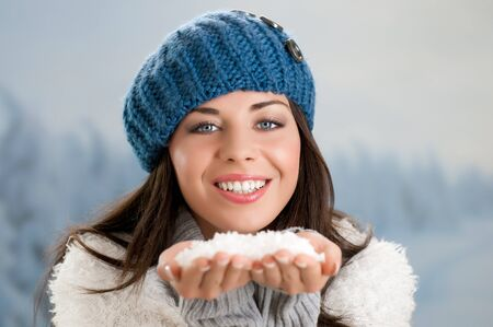 Happy beautiful young woman holding snowflakes ready to blow away in a winter day photo