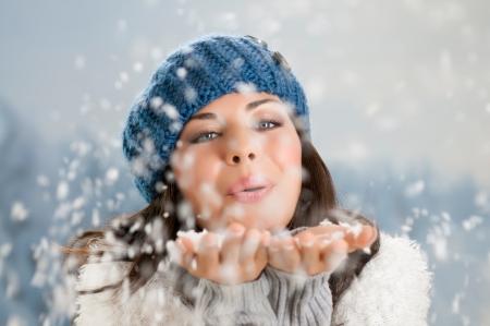 Feliz mujer joven y bella soplando copos de nieve de las manos en un día de invierno Foto de archivo