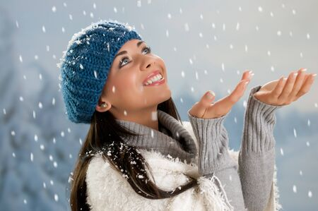Smiling beautiful young woman looking at falling snowflakes during a snowing winter day Stock Photo - 15155148