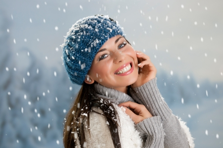 Happy beautiful girl smiling and looking at camera during a snowing day in winter Stock Photo - 15155153
