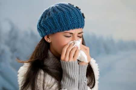 gripe: Mujer joven que consigue enfermo con gripe en un día de invierno al aire libre Foto de archivo