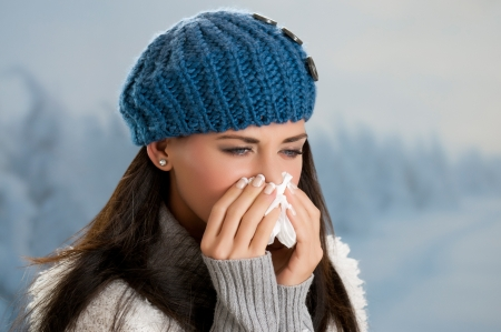 estornudo: Muchacha bonita que tiene gripe y fiebre en los días de invierno al aire libre