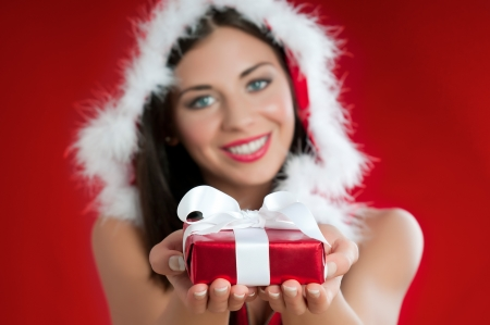 Smiling Santa Claus woman holding a wrapped gift for Christmas Stock Photo - 15155135