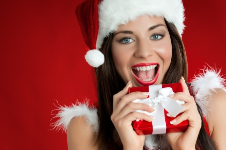 Happy joyful young woman in Santa Claus clothes holding and biting a red gift Stock Photo - 15155147
