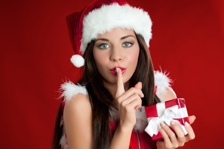 secretly: Santa Claus woman holding a present and carrying it secretly for Christmas Stock Photo