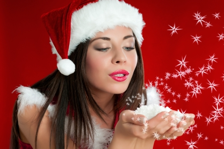 Beautiful Santa Claus woman blowing snowflakes and stars from her hands to celebrate the Christmas photo