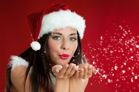 Beautiful santa claus girl blowing white snowflakes from her hands on red christmas background photo
