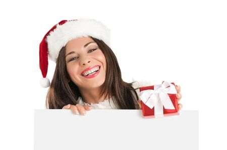 Smiling Christmas girl holding a gift and a white board ready for your text, isolated on white background Stock Photo - 15155132