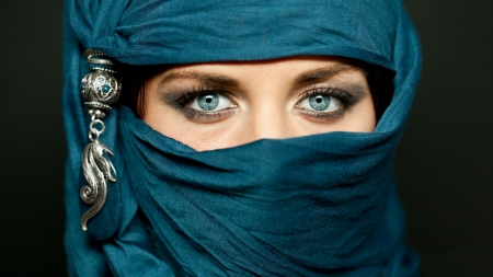 Portrait of an arabic young woman with her beautiful blue eyes in traditional islamic cloth niqab photo