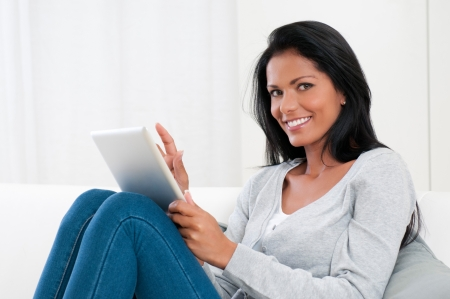 Smiling beautiful young woman relaxing with a digital tablet on sofa Stock Photo - 16126518