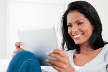 viewing: Bella giovane donna di relax a casa con la tavoletta digitale