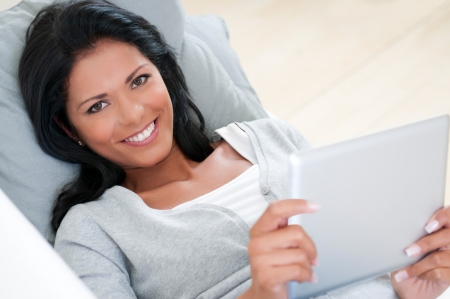 Happy smiling young woman relaxing on sofa with a digital tablet photo