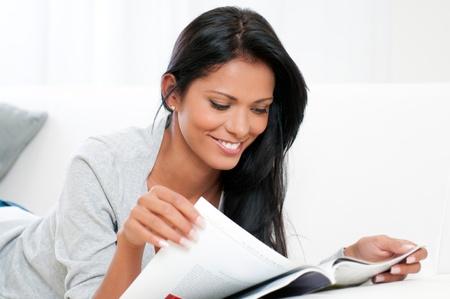 mujer leyendo libro: Hermosa mujer joven leyendo la revista y acostado en el sof� en casa