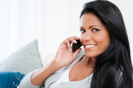 Beautiful young woman talking on mobile phone at home Stock Photo - 16126488