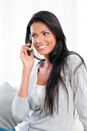 Beautiful young woman talking on mobile phone at home Stock Photo - 16126516