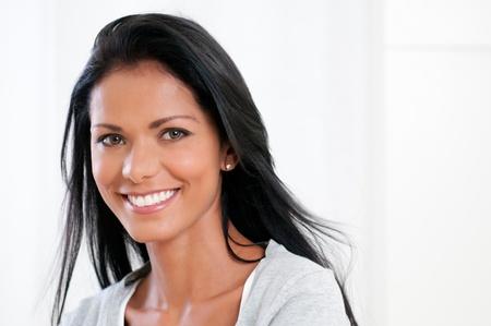 Mujer latina hermosa sonriente y mirando a cámara aislada sobre fondo blanco