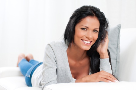 Beautiful young woman relaxing and lying on sofa at home Stock Photo - 16126510