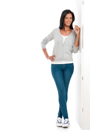 Beautiful young casual woman leaning on white wall isolated photo