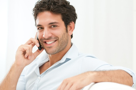 phone conversation: Good Looking Man Sitting On Sofa And Talking On Mobile Phone