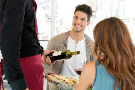Young Couple Having Meal At Restaurant And Waiter Serving Wine Stock Photo - 16732465