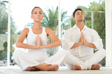 Young Couple Sitting In A Lotus Pose And Meditating While Exercising At Yoga  photo