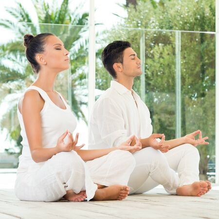 Young Couple Sitting In A Lotus Pose And Meditating  photo