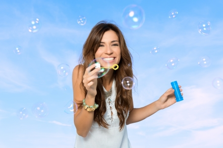 Beautiful Young Woman Blowing Soap Bubbles In a Summer Day Outdoor  photo