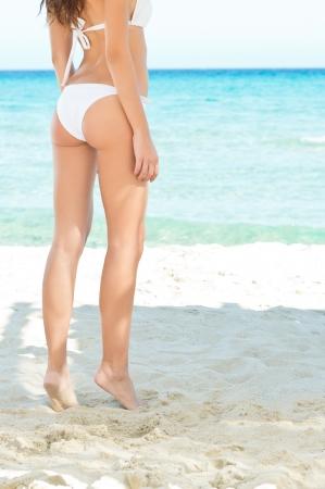 ni�as en bikini: Hermosas piernas delgadas en una playa tropical en verano