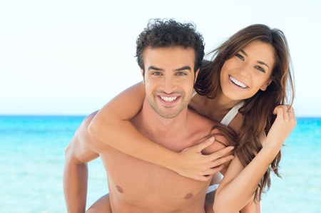 Smiling Young Man Piggybacking His Pretty Girlfriend On Summer Beach  photo