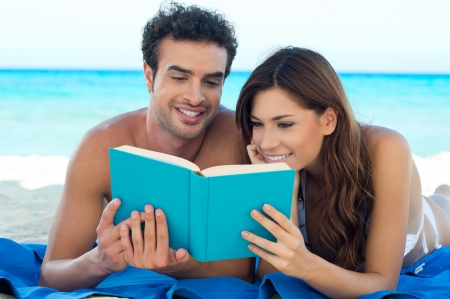 Portrait Of Happy Couple Reading Book On Summer Beach  photo