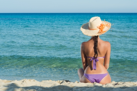 Young Woman Sitting And Looking At Sea photo