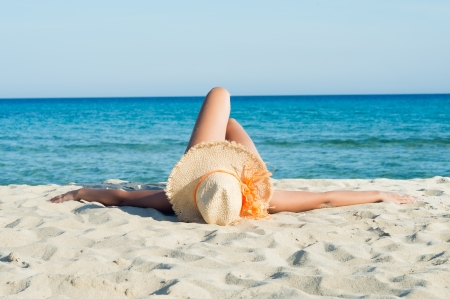 Young Woman Enjoying Sunbath On White Beach  photo