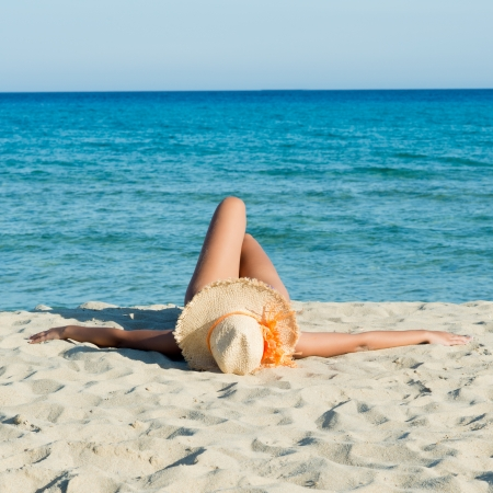 Young Woman Relaxing and Sunbathing At Beach photo