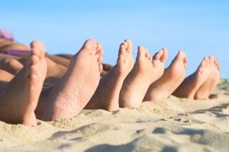 woman foot: Closeup of feet row lying in line at summer beach